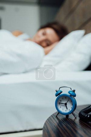 Photo pour Foyer sélectif de rétro réveil bleu près de la femme dormant dans le lit - image libre de droit