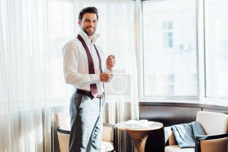 Photo pour Homme barbu joyeux en costume toucher chemise tout en se tenant à l'hôtel - image libre de droit
