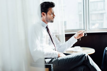 Photo for Selective focus of handsome bearded man in suit looking at watch while sitting near coffee table - Royalty Free Image