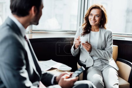 selective focus of cheerful businesswoman holding cup and looking at businessman with smartphone