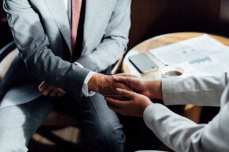 cropped view of business partners shaking hands in hotel