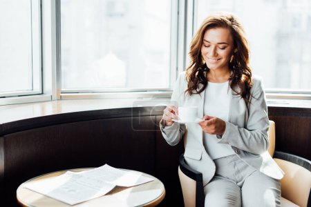 Photo for Cheerful businesswoman looking at cup with coffee while sitting near coffee table with newspaper - Royalty Free Image