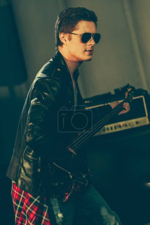 Photo for Stylish guitarist in sunglasses performing on stage - Royalty Free Image