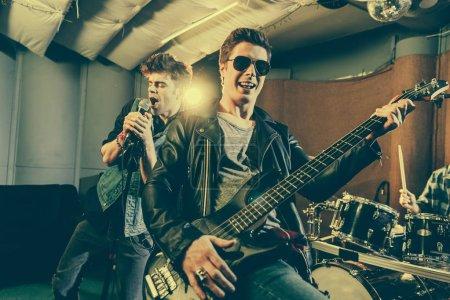 Photo pour Mise au point sélective du guitariste en jouant de la guitare électrique près du groupe de rock de lunettes de soleil - image libre de droit