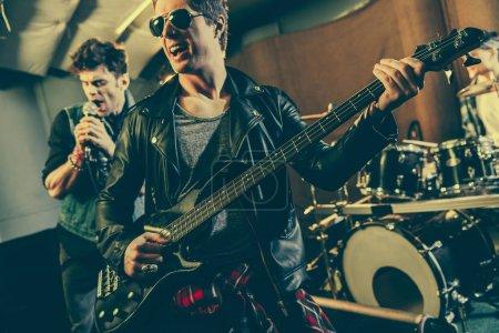 Photo pour Foyer sélectif du guitariste joyeux dans les lunettes de soleil jouant de la guitare électrique près du groupe de rock - image libre de droit