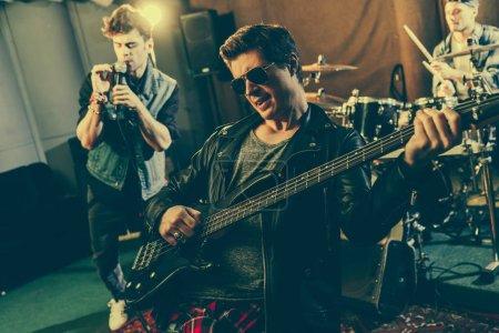 Photo pour Foyer sélectif du guitariste branché dans les lunettes de soleil jouant de la guitare électrique près du groupe de rock - image libre de droit
