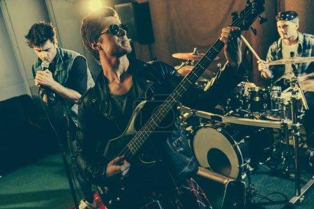 Photo pour Foyer sélectif de beau guitariste dans les lunettes de soleil jouer de la guitare électrique près du groupe de rock - image libre de droit