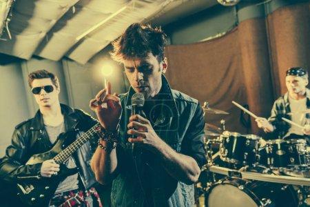 Photo pour Mise au point sélective de chanson chant homme tendance près de lunettes de soleil et batteur guitariste - image libre de droit