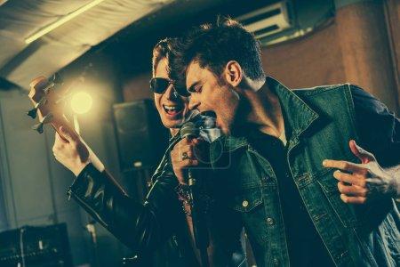 Photo pour Élégant chanteur chantant dans le microphone avec le beau guitariste dans lunettes de soleil - image libre de droit