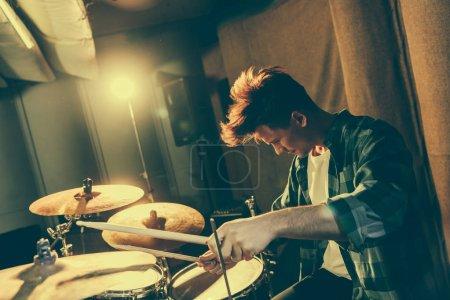 Photo pour Beau musicien tenant des baguettes tout en jouant de la batterie - image libre de droit