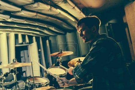 Photo pour Beau musicien tenant les baguettes et jouer de la batterie - image libre de droit