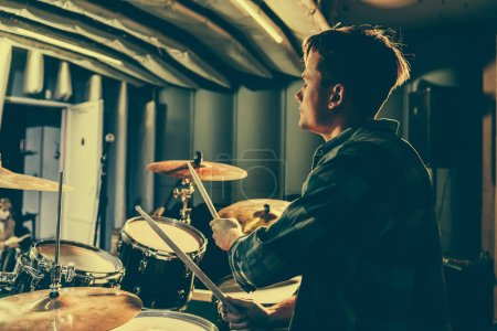 Photo for Good-looking musician holding drum sticks while playing drums - Royalty Free Image