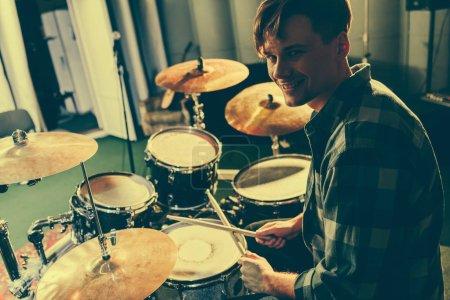 Photo pour Joyeux musicien beau tenant les baguettes près de batterie - image libre de droit