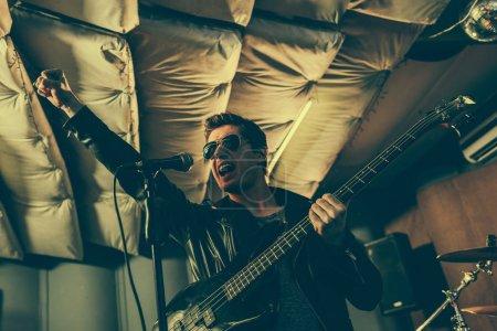 Photo pour Chanson chanter beau guitariste micro tout en tenant une guitare électrique - image libre de droit