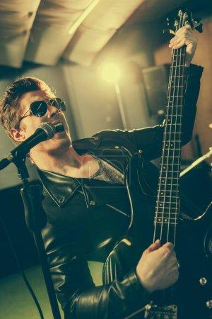 Photo pour Beau guitariste dans lunettes de soleil chant micro tout en jouant de la guitare électrique - image libre de droit