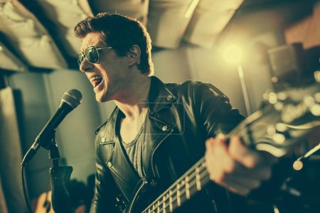 Photo pour Mise au point sélective du guitariste dans lunettes de soleil chant micro tout en jouant de la guitare électrique - image libre de droit