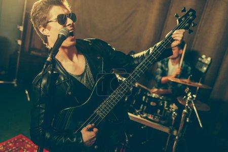 focus sélectif du guitariste jouant de la guitare électrique et chantant près du batteur
