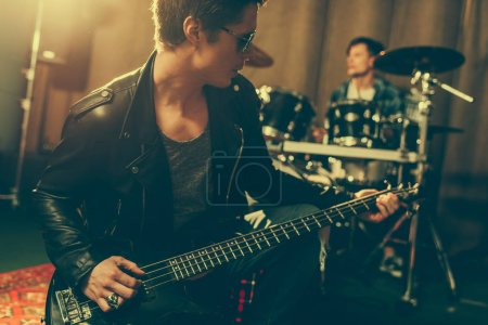 Photo for Stylish guitarist in sunglasses playing electric guitar near drummer - Royalty Free Image