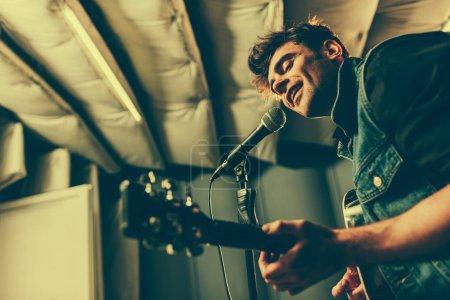 Photo pour Foyer sélectif du chanteur joyeux chantant dans le microphone tout en jouant de la guitare acoustique - image libre de droit