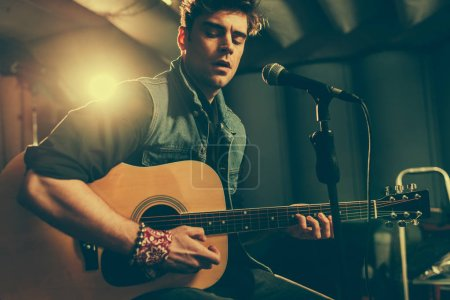 Photo for Handsome musician singing in microphone while playing acoustic guitar - Royalty Free Image