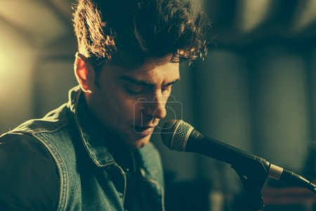 close up of good-looking musician singing in microphone