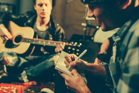 Photo pour Mise au point sélective du compositeur gaie écrire dans cahier près ami jouer de la guitare acoustique - image libre de droit