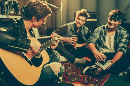 Foto de Enfoque selectivo de músico tocando guitarra acústica cerca amigos felizes sentado con las piernas cruzadas - Imagen libre de derechos