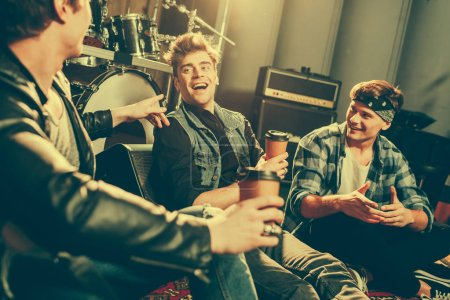 Photo for Selective focus of happy rock band laughing while talking and holding paper cups - Royalty Free Image