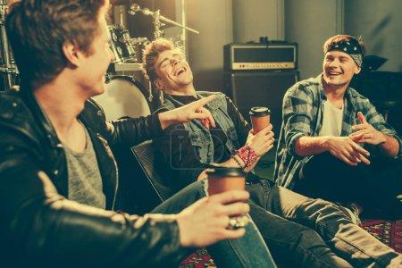 Photo pour Mise au point sélective de joyeux amis riant tout en parlant et en tenant les gobelets en papier - image libre de droit