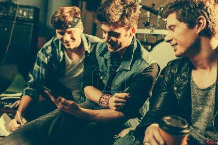 Photo pour Mise au point sélective d'homme tenant la tasse de papier près amis regardant smartphone - image libre de droit