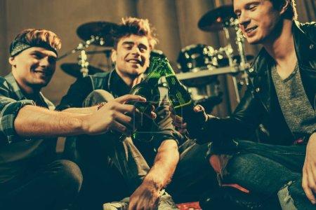 Photo pour Mise au point sélective d'amis joyeux cliquetis des bouteilles en verre de bière - image libre de droit