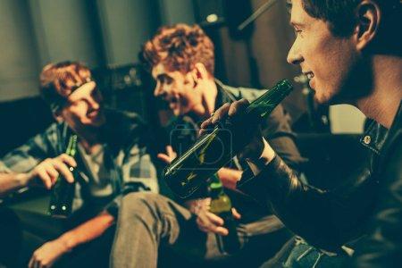 Photo pour Mise au point sélective de l'homme tenant la bouteille avec de la bière et à la recherche d'amis - image libre de droit