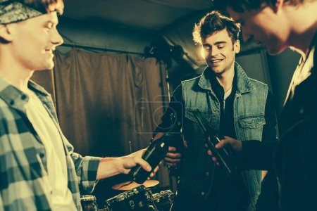 Photo pour Mise au point sélective de bouteille sonnante homme gai avec des amis - image libre de droit