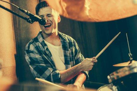 Photo pour Mise au point sélective de bel homme chantant dans le microphone tout en jouant de la batterie - image libre de droit