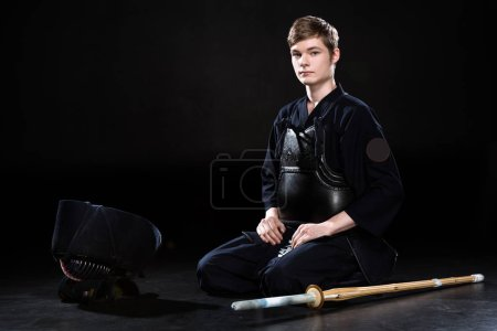 Photo for Handsome young man in kendo armor with bamboo sword sitting on black - Royalty Free Image
