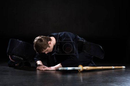 Photo for Kendo fighter with sword and helmet bowing on floor on black - Royalty Free Image