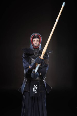 Photo for Kendo fighter in armor practicing with bamboo sword on black - Royalty Free Image