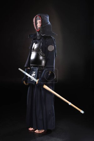 Photo for Full length view of kendo fighter in armor holding bamboo sword on black - Royalty Free Image