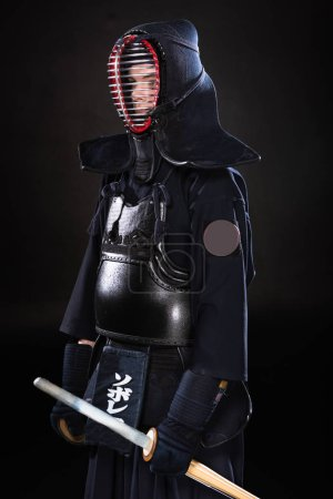Photo for Kendo fighter in armor holding bamboo sword on black - Royalty Free Image