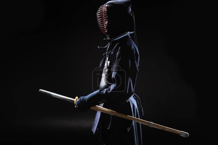 Side view of kendo fighter in traditional helmet h...