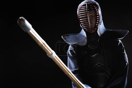 Photo for Kendo fighter in armor practicing with bamboo sword isolated on black - Royalty Free Image