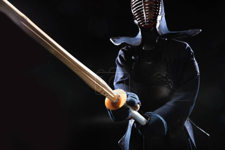 Photo for Kendo fighter in helmet holding bamboo sword on black - Royalty Free Image