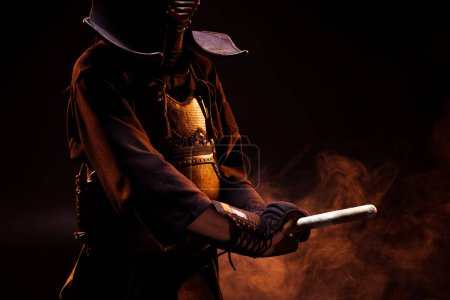 Photo for Partial view of kendo fighter in armor holding sword on black - Royalty Free Image