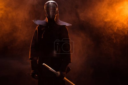 Photo for Kendo fighter in armor holding bamboo sword in smoke - Royalty Free Image