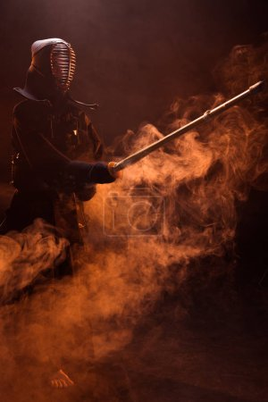 Photo for Kendo fighter in armor practicing with bamboo sword in smoke - Royalty Free Image