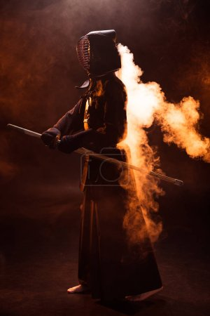 Photo for Full length view of kendo fighter in armor holding bamboo sword in smoke - Royalty Free Image
