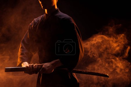 Photo for Cropped view of young man in kimono holding kendo sword in smoke - Royalty Free Image