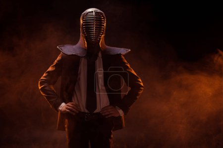 Photo for Kendo fighter in formal wear and helmet standing with arms akimbo on dark - Royalty Free Image