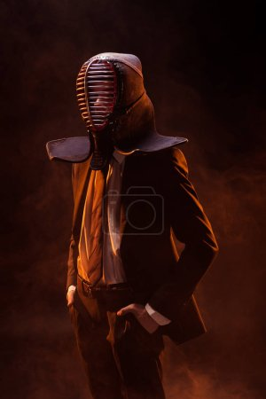 Photo for Confident kendo fighter in formal wear and helmet standing with hands in pockets on dark - Royalty Free Image