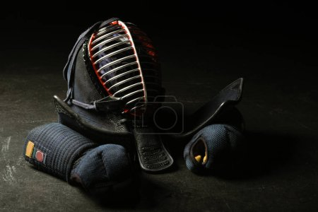 Photo for Kendo gloves and traditional helmet on dark surface - Royalty Free Image